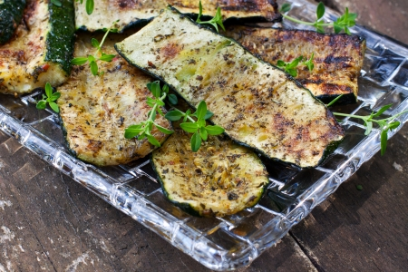 Grilled zucchini garnished with thyme on wooden background