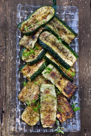 Grilled zucchini garnished with fresh thyme on wooden background Stock Photo