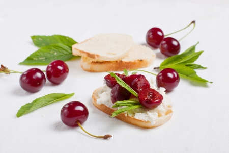 Crostini with coft cheese and cherry compote garnished with mint leaves