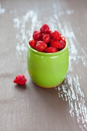 Fresh wild strawberries in a green ceramic jar on brown wooden background, selective focus Stock Photo