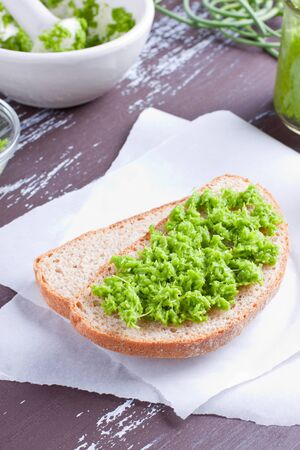 Green garlic pesto on bread Stock Photo