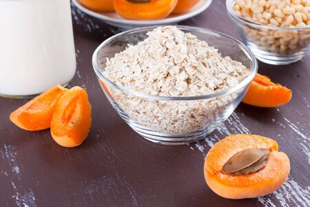 Dry oatmeal in a glass bowl with cut apricots Stock Photo
