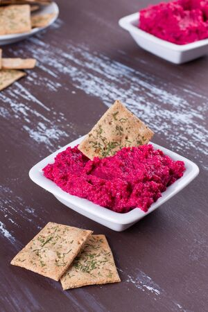Portion of beetroot hummus with crackers