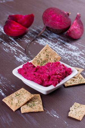 Portion of beetroot hummus with  cut beetroot on background Stock Photo