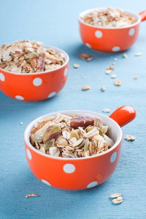 Three orange bowls full of muesli with various nuts photo