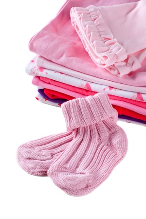 Pile of pink baby girl clothes with pair of socks in front of it, isolated over white