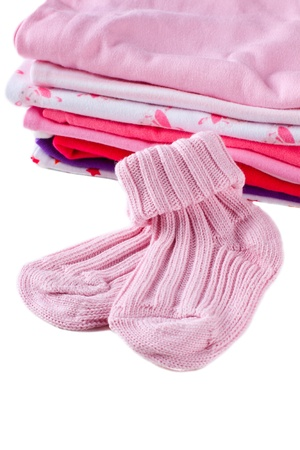 Pink socks for baby girl in front of pink clothes stack, isolated over white