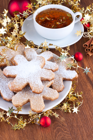 Plate of snowflake shaped cookies and a cup of herbal tea with christmas decoration