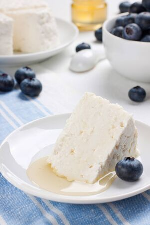 Close up of cottage cheese with fresh blueberry and honey