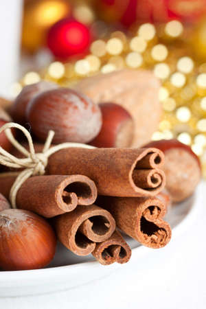 Group of cinnamon sticks and nuzelnuts on festive christmas background, shallow depth of field photo
