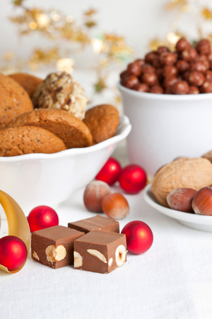 Hazelnut chocolate with cookies and bright christmas baubles