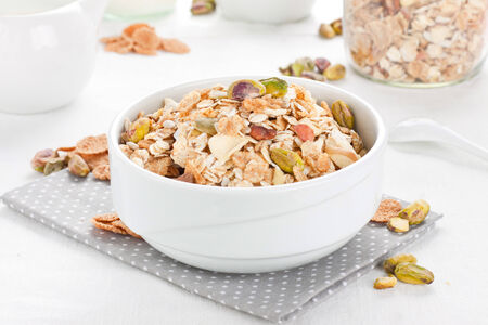 Muesli with various nuts in white bowl Stock Photo