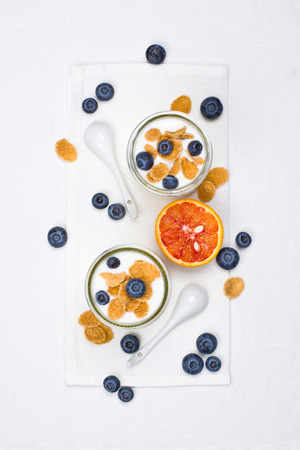 Yogurt in glasses with berries and cornflakes photo