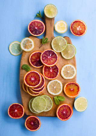 cutting bord: Assorted cut citrus fruits on cutting bord shot from above on light blue background