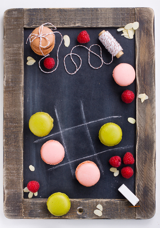 French macaroons on chalkboard with fresh raspberries shot from above photo