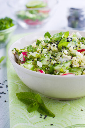 Bowl full of fresh couscous salad with cucumber and radish