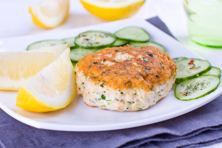 Close up of a salmon patty served woth cucumber and lemon Stock Photo