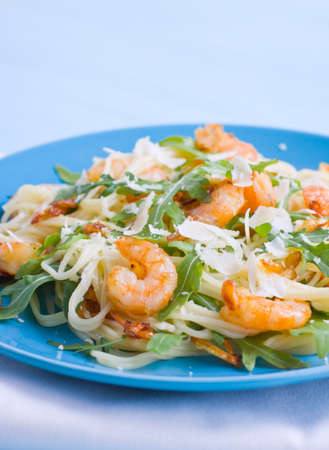 Close up of pasta cooked with shrimps and arugula Stock Photo