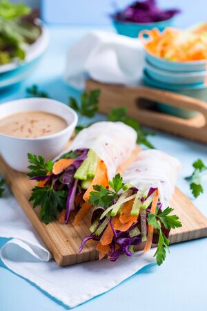 Vegetarian spring rolls served on a wooden board with sauce Stock Photo