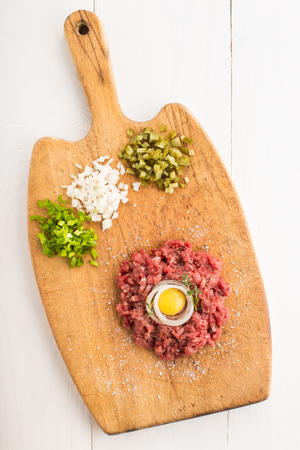 Delicious tartare made of raw beef and served with onions and pickled cucumbers