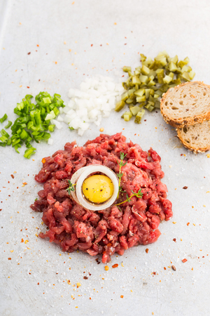 Beef tartare served with bread, minced onions and cucumbers Stock Photo