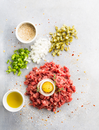 Raw beef tartare with salt, oil and vegetables