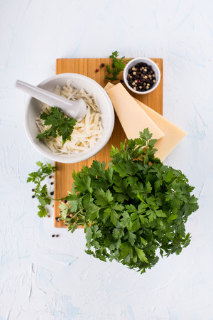 Grated cheese in a mortar and green herbs
