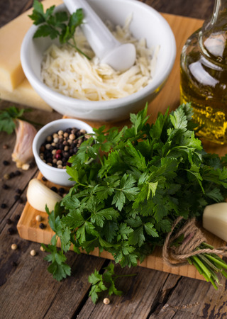 Fresh parsley with some other pesto ingredients on wooden background