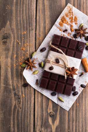 Dark chocolate with spices on wooden background Stock Photo