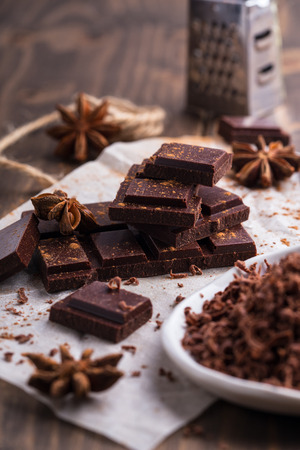 Heap of chocolate pieces with anise and small grater on the background
