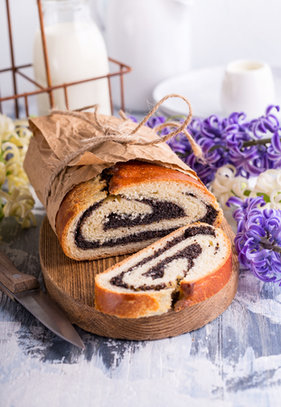Sweet cake with poppy seed fillig on wooden board Stock Photo