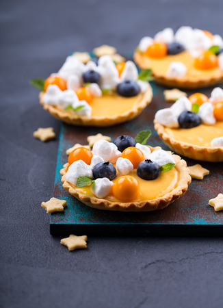 Lemon curd tartlet decorated with italian meringue and fresh berries
