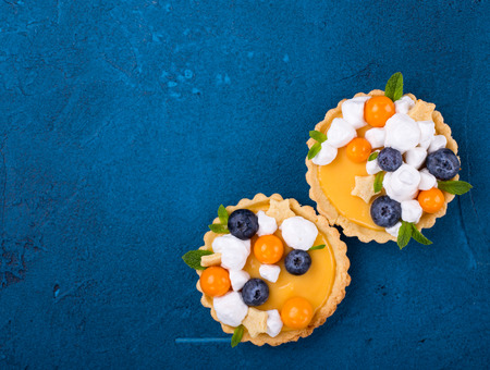 Two lemon tartlets on blue background with space for text