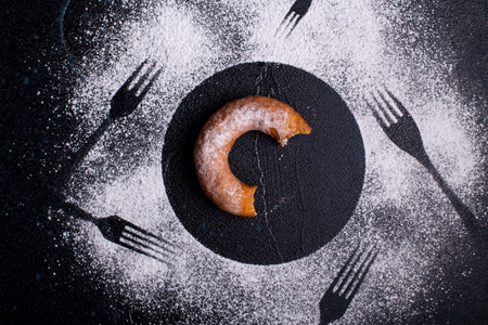 Piece of doughnut surrounded with forks Stock Photo