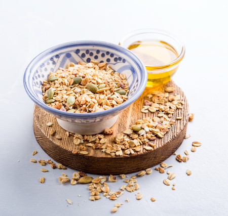 Close up of a bowl with granola and some honey