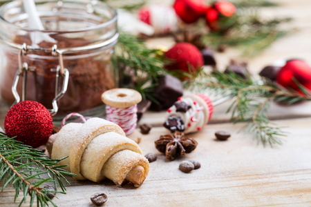 Festive Christmas composition with fir tree brunches, red baubles and a homemade cookie