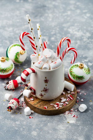 Mug of hot cacao loaded with marshmellows and some festive decorations on background
