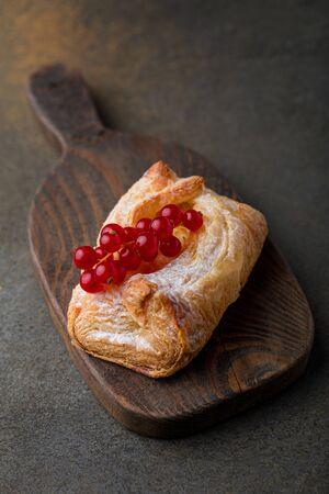 Fresh tasty sweet bun on a wooden board
