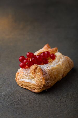 Sweet puff pastry roll decorated with red currant