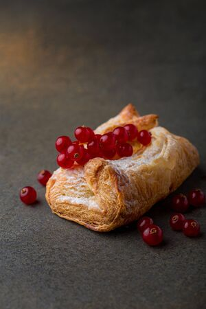 Freshly baked puff pastry bun garnished with sugar powder and berries