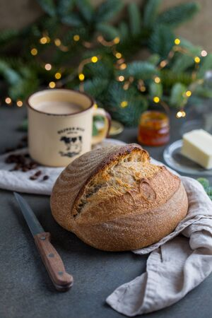 Artisan loaf of bread with fir branches and Christmas lights on background