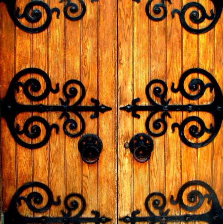 Old doorway with black wrought iron hinges Stock Photo