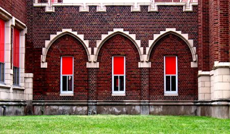 Three arches with red window shades set against red brick walls photo
