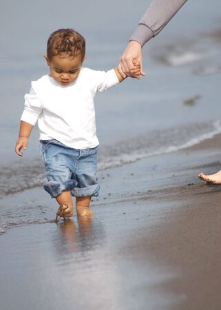toddler walking: Male toddler walking along the beach holding his mothers hand Stock Photo