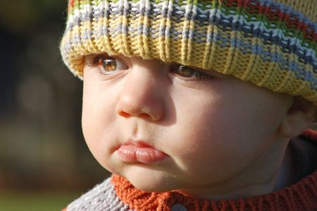Close up shot of a young boy outdoors in a sweater and wool cap Stock Photo