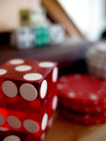 Close up of a red die with more dice and poker chips in the background photo