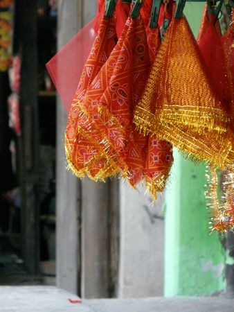 Red and gold hindu scarves hanging in a market stall photo