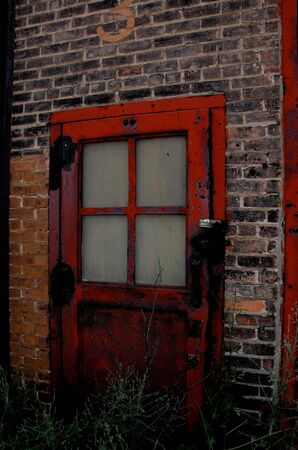 Old, weathered red door on the side of an abandoned building photo