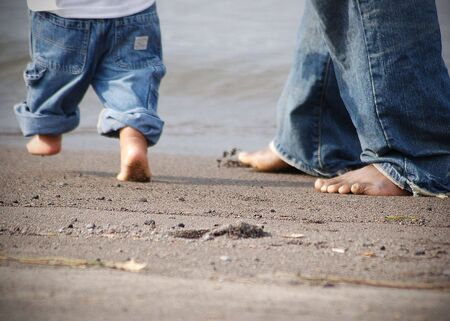 Shot focusing on father and sons feet at the beach together. Shot contains their feet and jeans against the brown sand of the beach