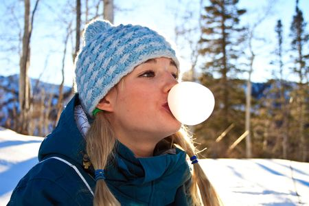 Young blond woman with pigtails outdoors in the snow blowing a bubble with her gum Stock Photo - 2650834